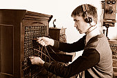 Young man operating vintage telephone equipment
